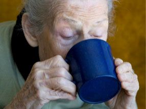 Elderly woman drinking from mug