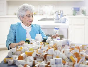 Senior woman with mountain of pill bottles