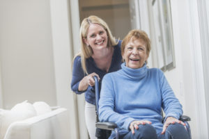 senior laughing while being assisted by caregiver