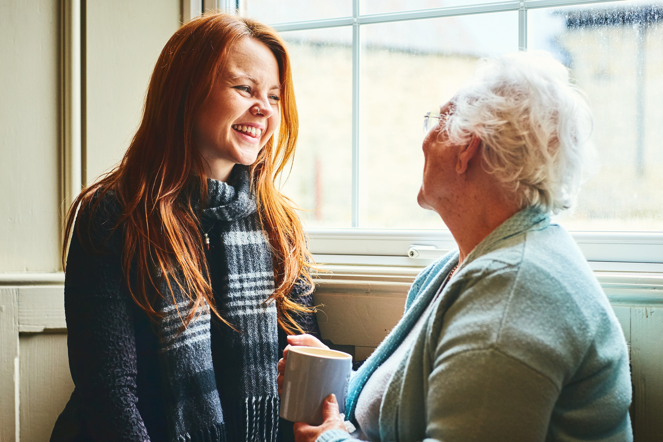 Young caregiver talks to senior woman about the advantages of home health care.