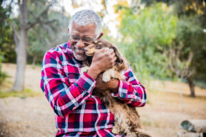 older man holding a playful puppy to help relieve senior stress