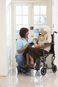 Caregiver With Disabled Senior Woman Sitting In Wheelchair